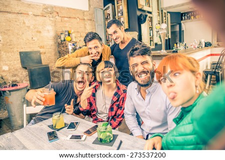 Group of friends having fun in a cocktail bar and taking a selfie - Young students partying together and taking picture - Concepts about fun,youth,technologies and nightlife
