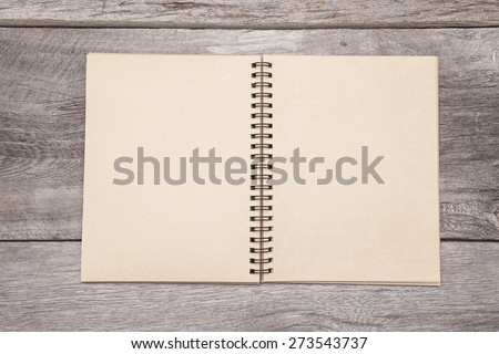 A blank recycled paper scrapbook sits on a rustic wooden background.  Royalty-Free Stock Photo #273543737