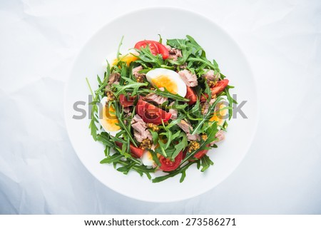 Fresh salad with tuna, tomatoes, eggs, arugula and mustard on white textured background top view. Healthy food. #273586271