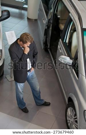 Young man examining new car at showroom #273679460
