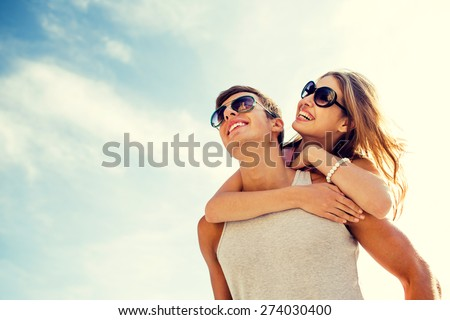 holidays, vacation, love and friendship concept - smiling couple having fun over sky background #274030400