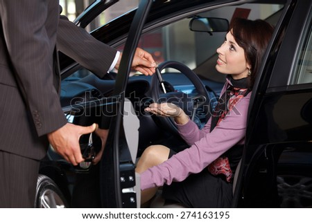 Car salesman giving the car keys to a young woman #274163195