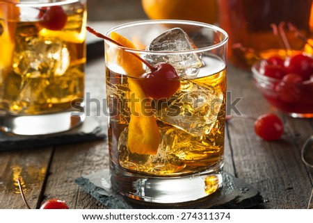Homemade Old Fashioned Cocktail with Cherries and Orange Peel Royalty-Free Stock Photo #274311374