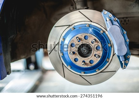 Front disc brake on car in process of new tire replacement Royalty-Free Stock Photo #274351196
