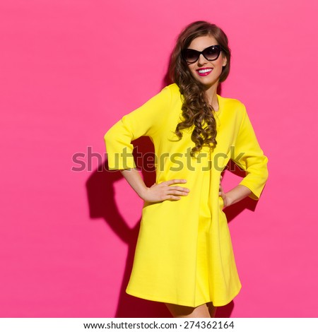 Smiling Fashionable Girl Against Pink Wall. Smiling beautiful girl in yellow mini dress posing against pink background. Three quarter length studio shot. #274362164