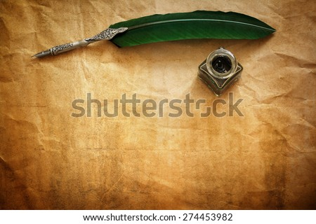 Quill pen and ink well resting on blank parchment paper with copy space for message Royalty-Free Stock Photo #274453982