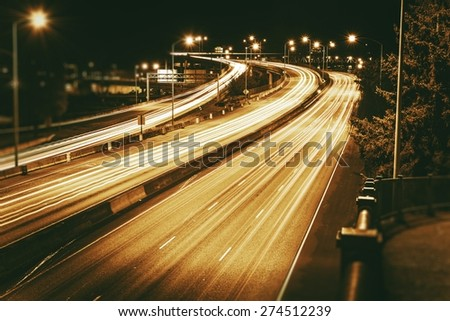 American Highways System at Night. Traffic in Motion. Long Exposure Photo. Dark Sepia Color Grading.