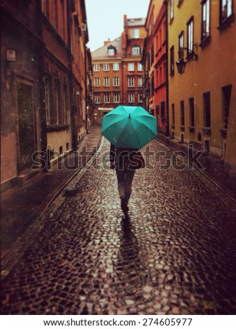 Woman with umbrella walking on the rain in old town of Warsaw, Poland. Vintage edited picture
