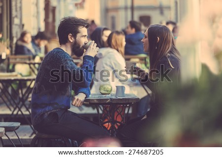 Hipster couple drinking coffee in Stockholm old town. They're sitting face to face. The man is wearing a blue sweater and the woman a striped shirt with black leather jacket. See-through shot. Royalty-Free Stock Photo #274687205