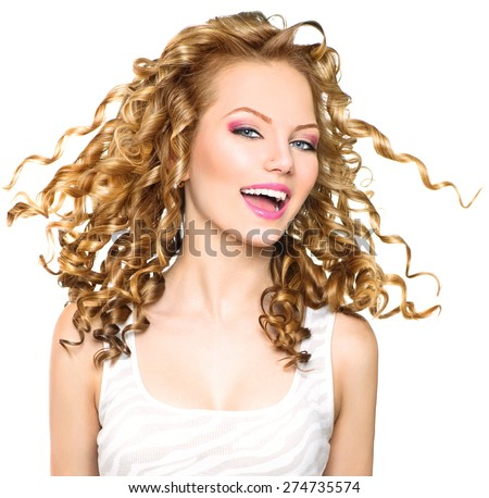 Beauty model girl with blowing Blonde curly hair. Portrait isolated on white background. Healthy wavy hair. Hairstyle. Beautiful smiling young woman. Beautiful face, natural make up. Long permed hair #274735574