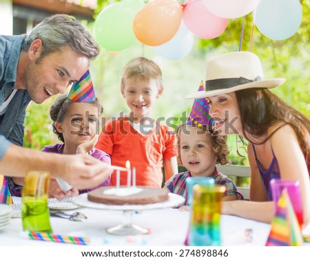 garden party with family for little girl's birthday, Dad lights the candles on the cake , the garden is decorated with balloons and colors are bright #274898846
