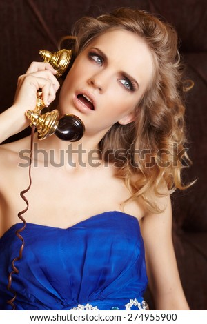 Blond female in blue dress speaking on phone #274955900
