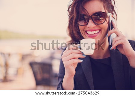 Young woman at cafe drinking coffee and talking on the mobile phone #275043629