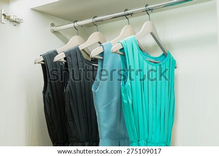 row of colorful dress hanging on coat hanger in white wardrobe #275109017