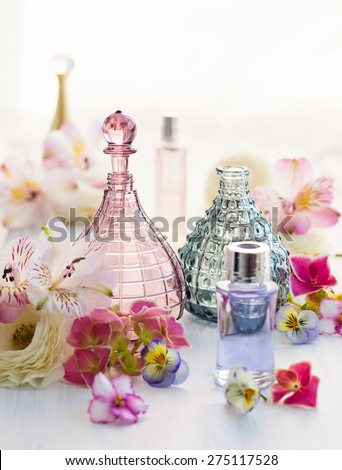 perfume and aromatic oils bottles surrounded by fresh flower #275117528