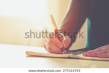 female hands with pen writing on notebook Royalty-Free Stock Photo #275161592