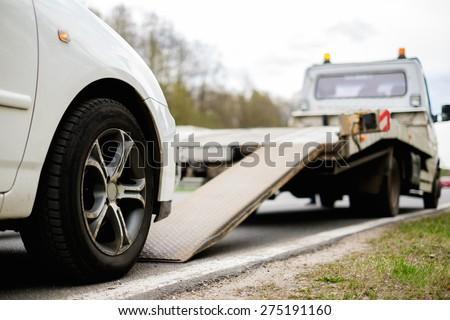 Loading broken car on a tow truck on a roadside  #275191160
