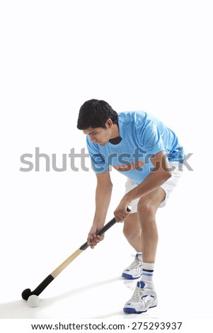 Young man in sportswear playing hockey isolated over white background