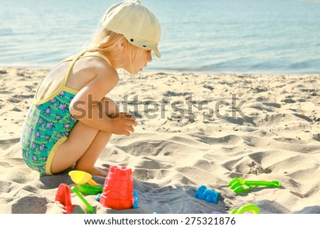 little girl playing on the sea shore #275321876