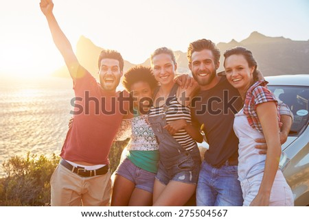 Group Of Friends Standing By Car On Coastal Road At Sunset #275504567