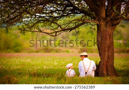father and son sitting under the tree on spring lawn Royalty-Free Stock Photo #275562389