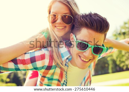 holidays, vacation, love and friendship concept - smiling couple having fun in park #275610446