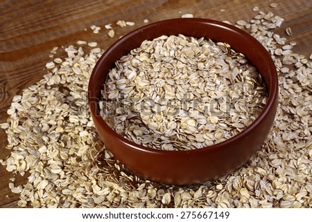 Oatmeal in plate and on wooden table top, horizontal photo #275667149
