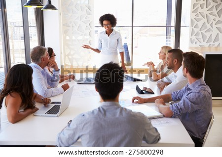 Businesswoman presenting to colleagues at a meeting Royalty-Free Stock Photo #275800298