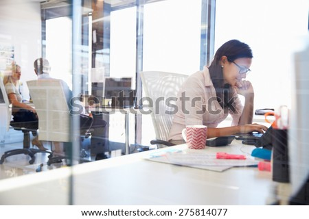 Woman working at computer in an office Royalty-Free Stock Photo #275814077