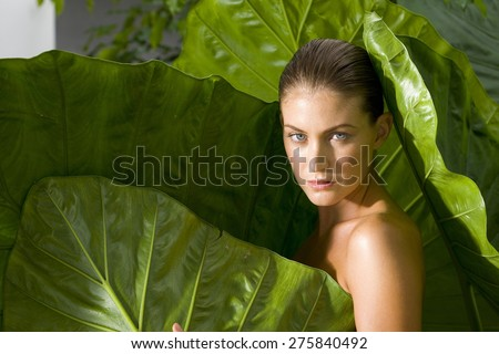 Naked woman emerging from giant leaves. #275840492