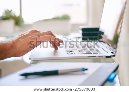 close up of a hand scrolling on a notebook, with copy space and a digital tablet in the foreground and hard drives in the background #275873003