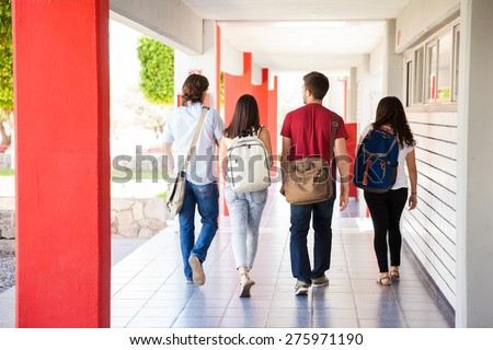 Rear view of a group of university students walking away on a school hallway Royalty-Free Stock Photo #275971190