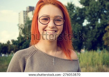 Girl with bright red hair. Woman in glasses. Beautiful happy girl outdoors. Beautiful smile on her face. Girl looks straight ahead at you. woman on the background of sky and green plants. Funny face. #276053870