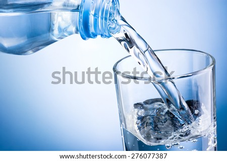 Close-up pouring water from bottle into glass on a blue background #276077387