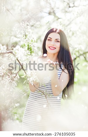 portrait of young lovely woman in spring flowers #276105035
