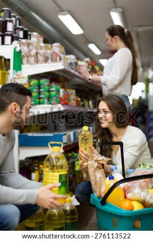 Young smiling family selecting vegetable oil at grocery store. Focus on girl #276113522