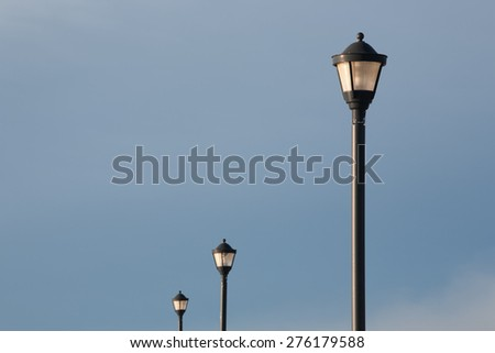 Street lamp and sky during daylight with two lamps in background. #276179588