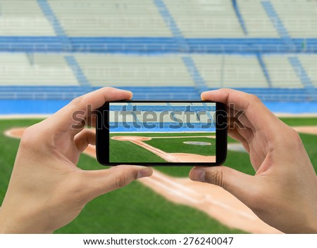 hand the tourist takes a picture with his mobile of the baseball stadium