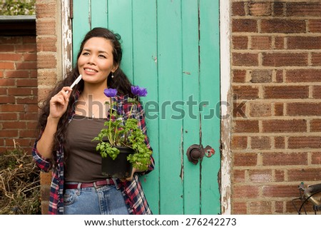 young woman holding a plant thinking #276242273