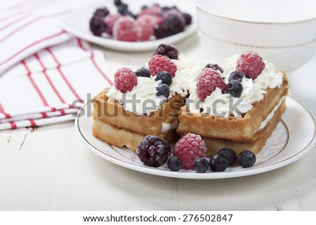 Soft waffles with protein cream, berry jam, whipped cream and berries. #276502847