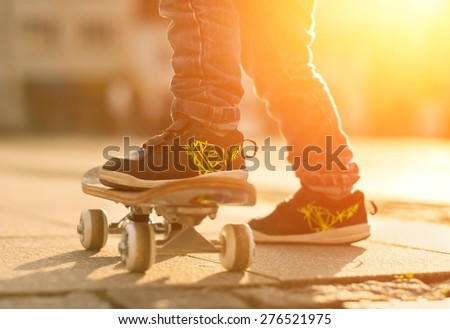 Child with skateboard on the street at sunset light. #276521975