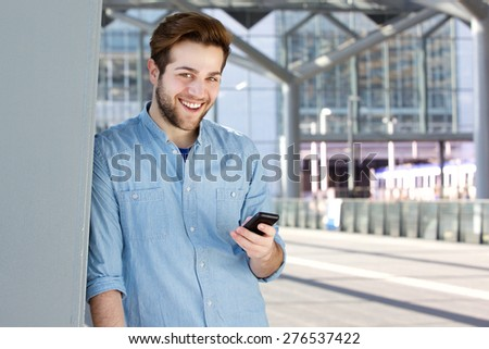 Close up portrait of a cool guy smiling with mobile phone #276537422