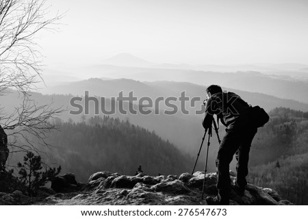 Professional photographer  on location takes photos with mirror camera on peak of rock. Dreamy fogy landscape, spring orange pink misty sunrise in a beautiful valley below. Black and white photo