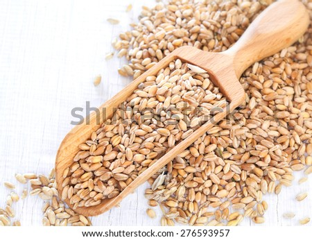 Full wooden scoop of sesame seeds on white wooden background #276593957