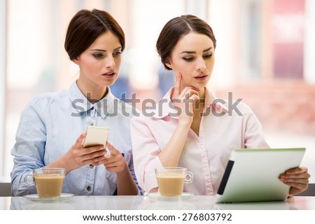 Two young beautiful businesswomen  sitting in urban cafe and using digital tablet. #276803792