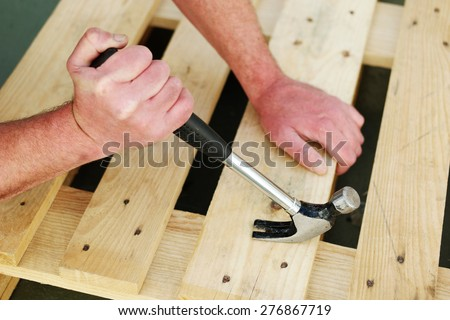 Carpenter using a claw hammer to nail down wooden slats on a frame, close up of his hands and the hand tool #276867719