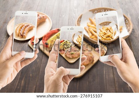 friends using smartphones to take photos of sausage and pork chop and french fries.
