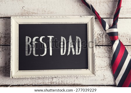 Rectangle picture frame with Best dad sign and colorful tie laid on wooden floor backround.