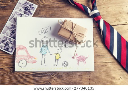 pictures of father and daughter, childs drawing, present and tie laid on wooden desk backround.