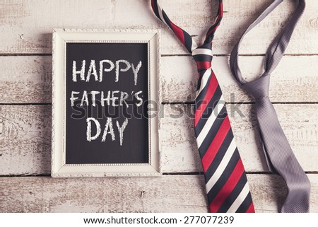 Rectangle picture frame with Happy fathers day sign and two ties laid on wooden floor backround.